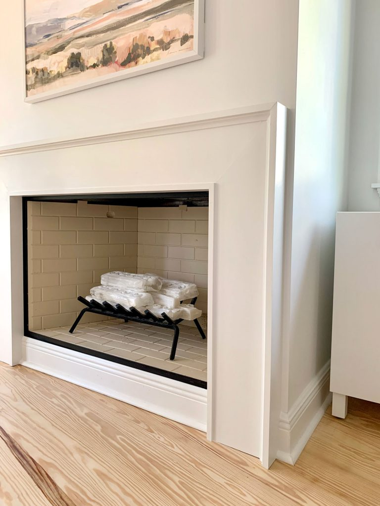 Closer view of fireplace surround  showing about an inch of drywall between it and corner of wall