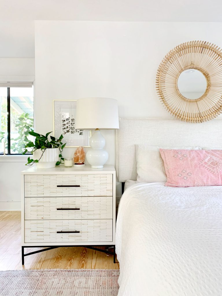 Linen headboard on bed with white bedding and inlay dresser as nightstand