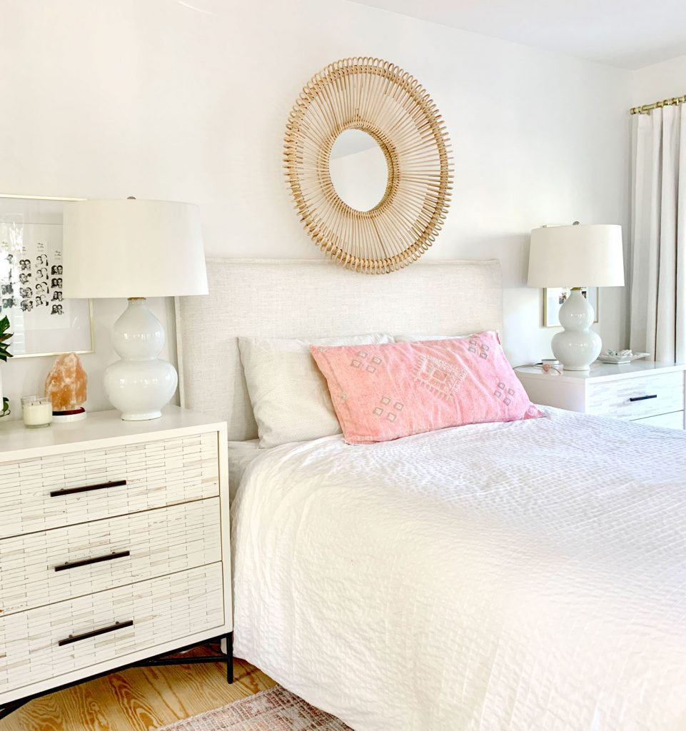 Linen headboard on bed with white bedding and round wicker mirror over headboard