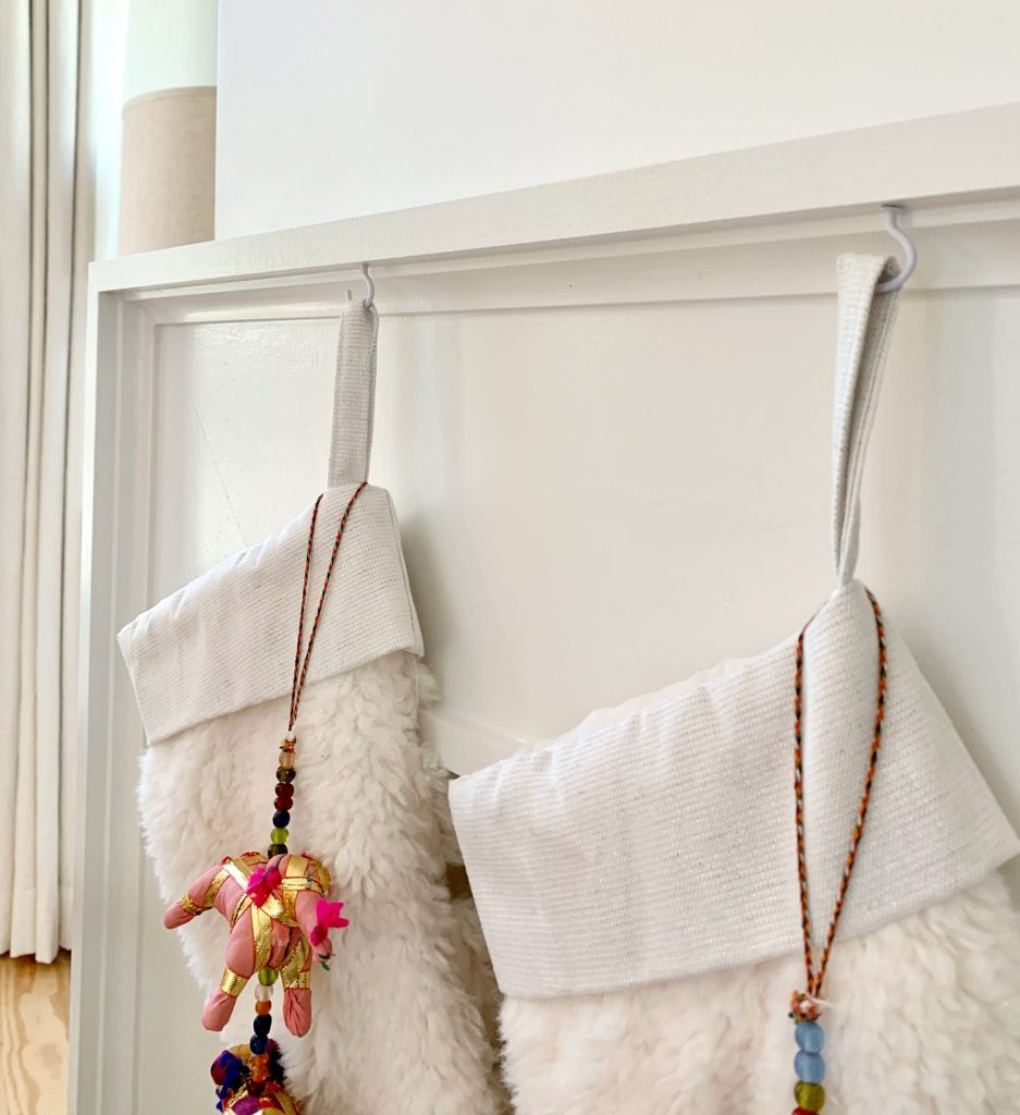 Close up detail of stockings hanging from mantel using small white cup hooks