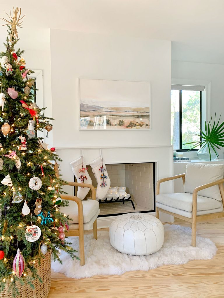 Christmas tree next to seating area in front of finished modern fireplace