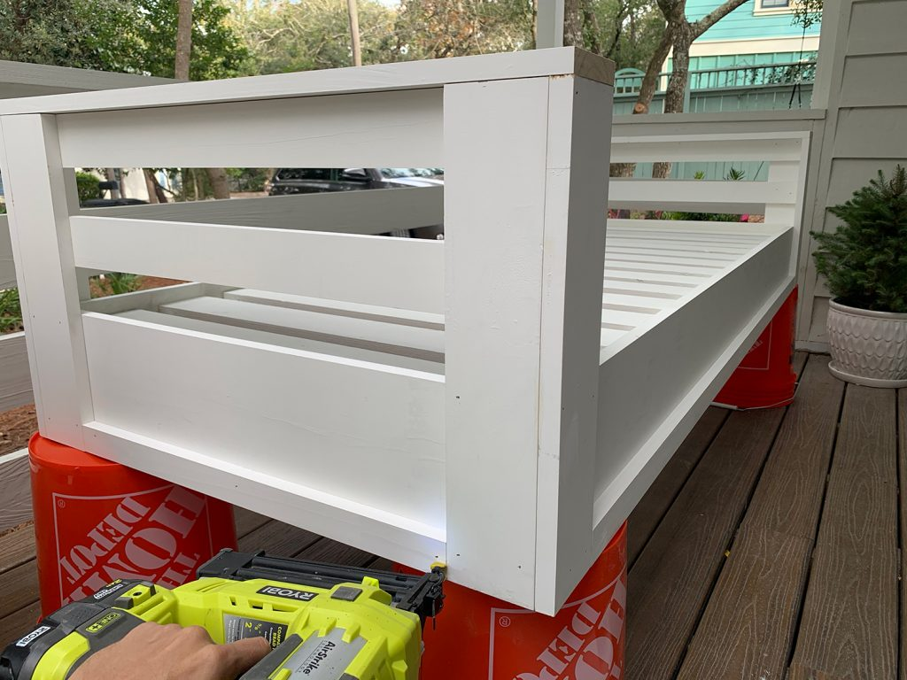 Nailing 1x2 trim piece along the bottom edge of hanging daybed