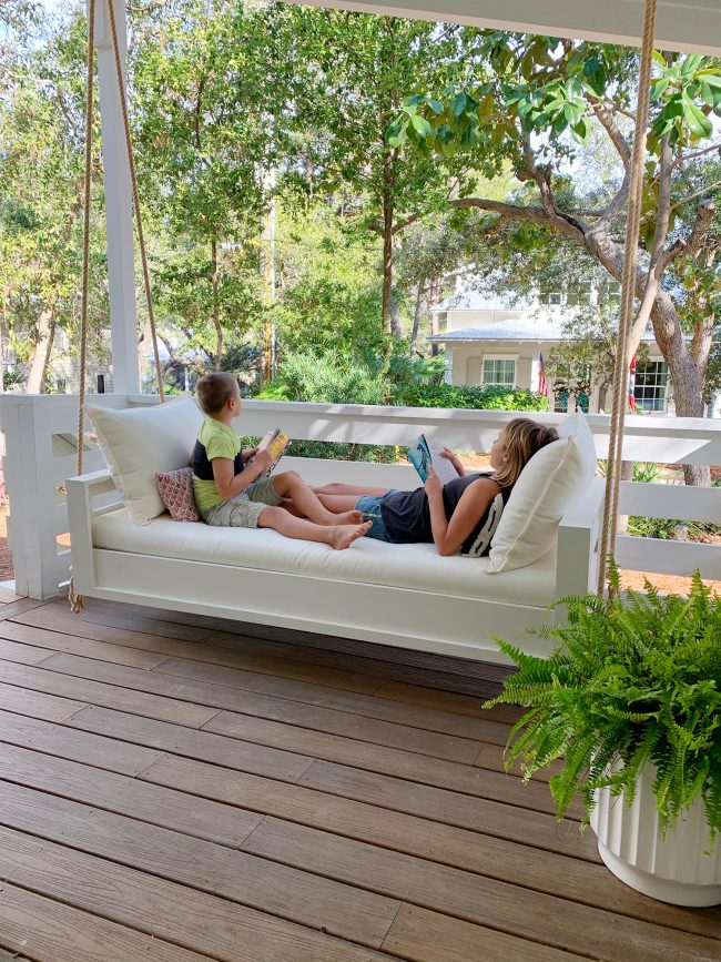 Two Kids Reading On Either End Of White Hanging Daybed Swing