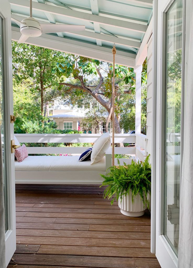 View Of White Hanging Daybed Swing Under Covered Porch Through Open French Doors