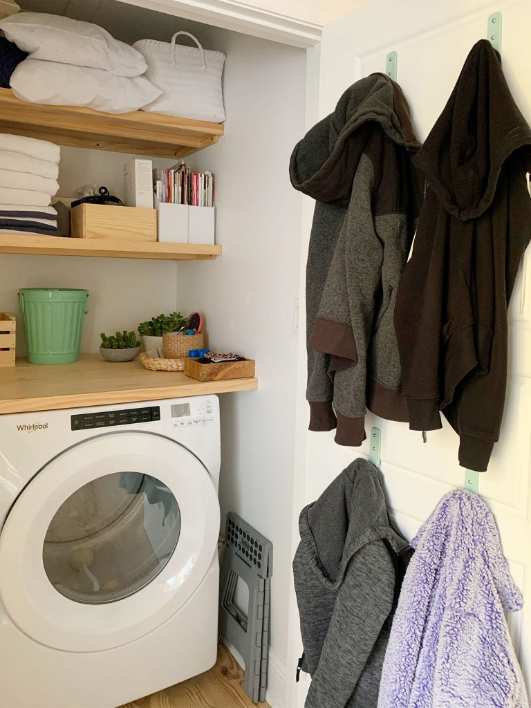 Coats hung on back of laundry closet door