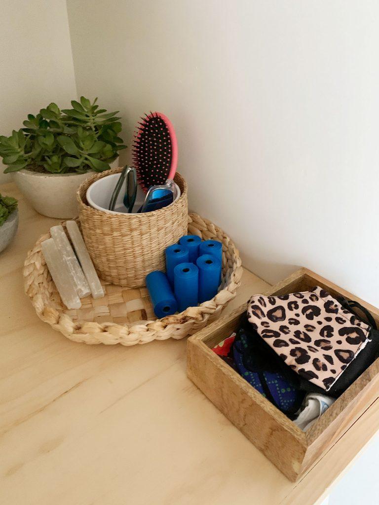 Kosarak és kukák a mosodai polcon, ahol bejárati kiegészítők találhatók, mint például maszkok, kutyatáskák és napszemüvegek