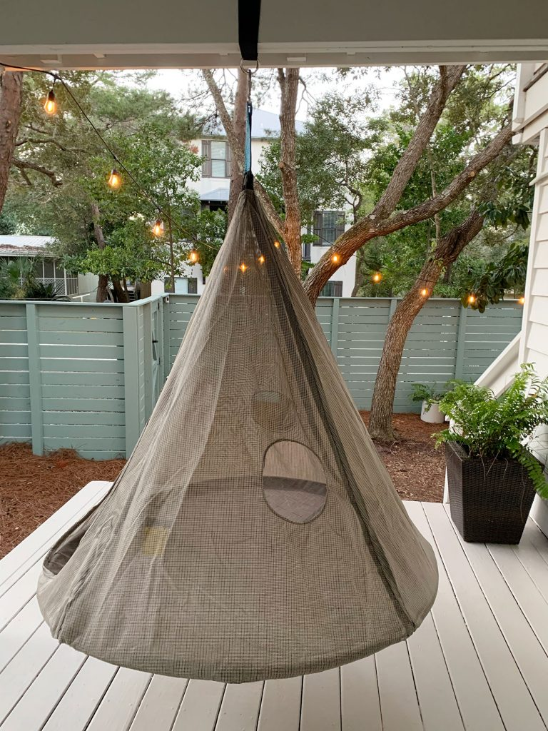 Hanging cone shaped netted tent above painted porch floor