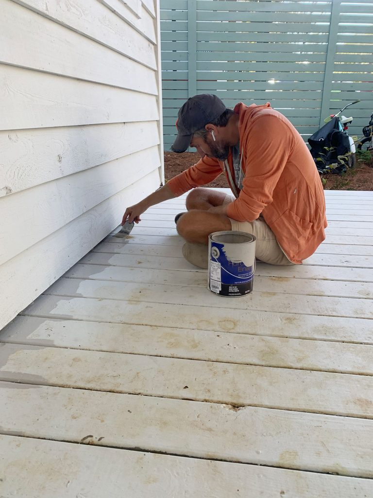 John edging porch floor with gray floor paint on paintbrush