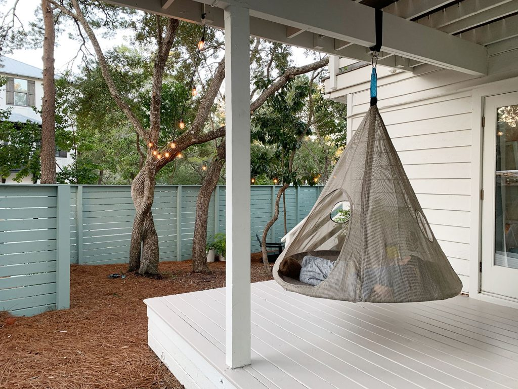 Two kids laying in hanging tent on covered porch