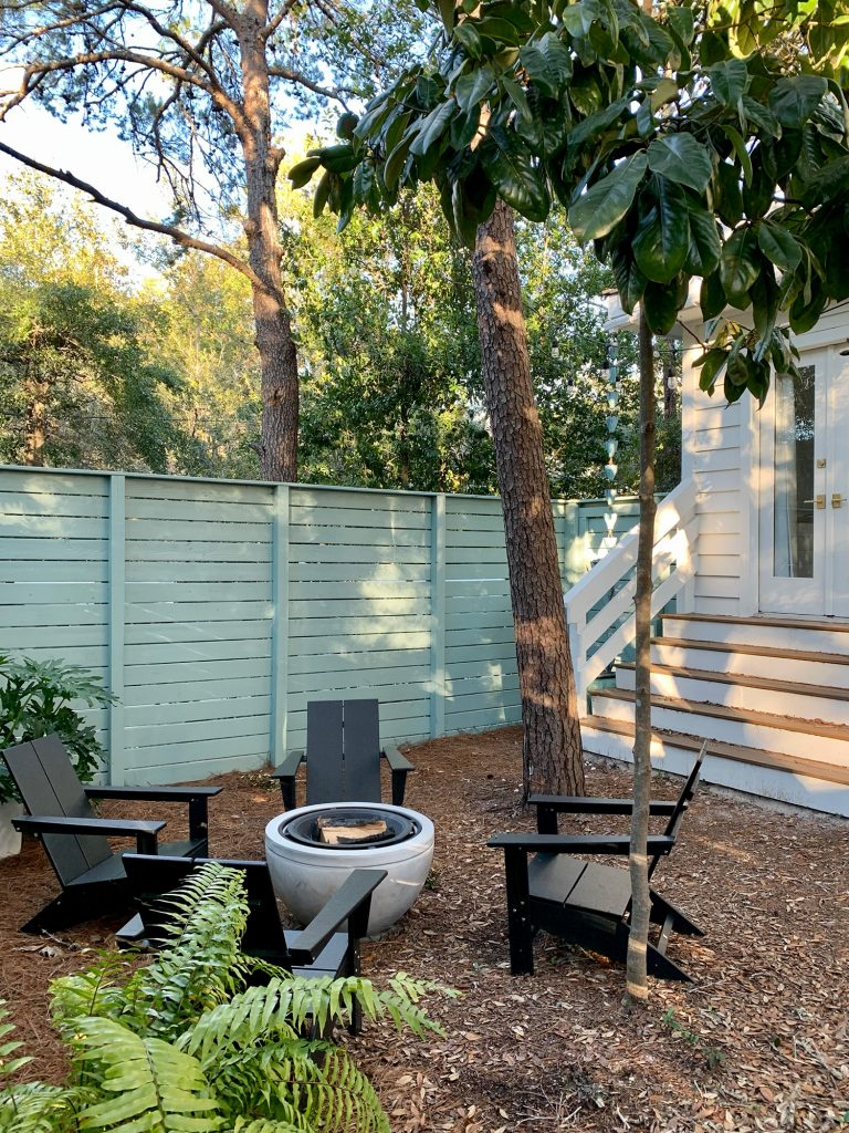 Trees around fenced side yard with black Adirondack chairs around fire pit