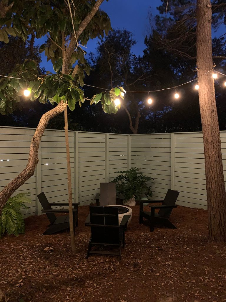 Nighttime view of fenced side yard with black Adirondack chairs around fire pit