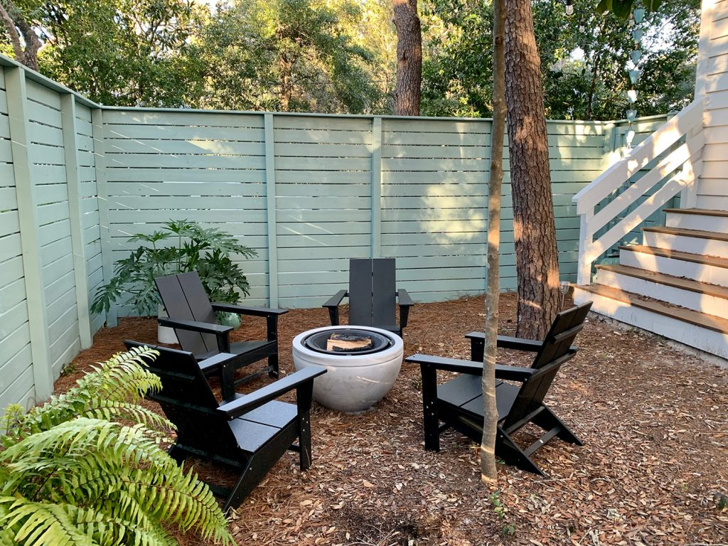 Painted fenced side yard with black Adirondack chairs around fire pit with potted plants