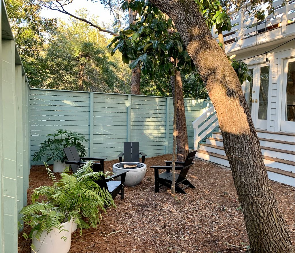 Green fenced side yard with black Adirondack chairs around fire pit