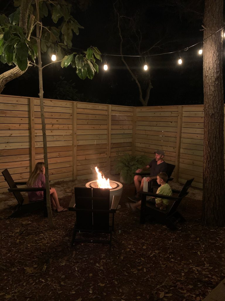 Family sitting around fire pit with unpainted fence