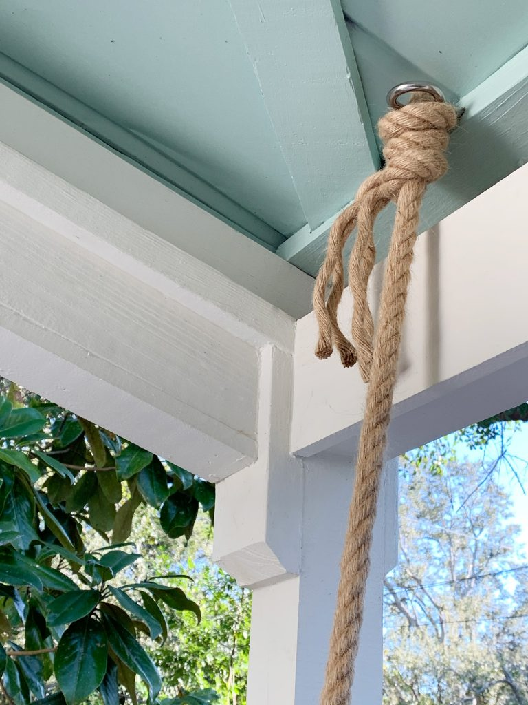 Rope knotted around screw eye hook in ceiling of covered porch