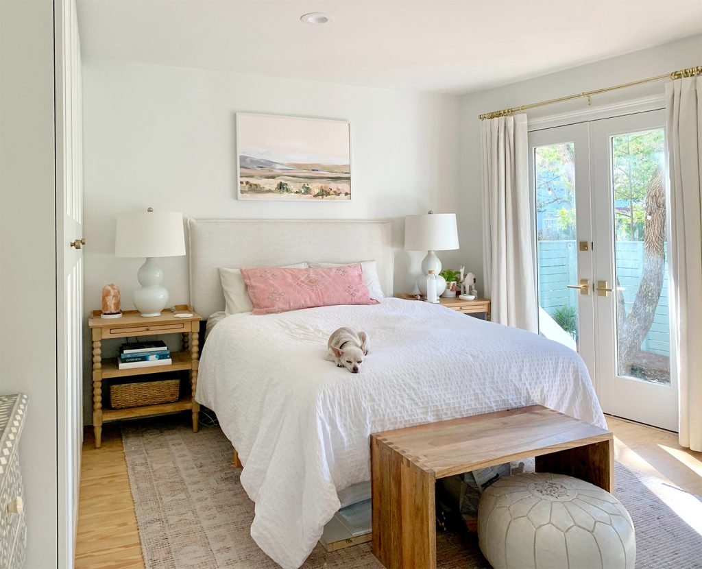 Bedroom with pink rug with french doors next to white bed