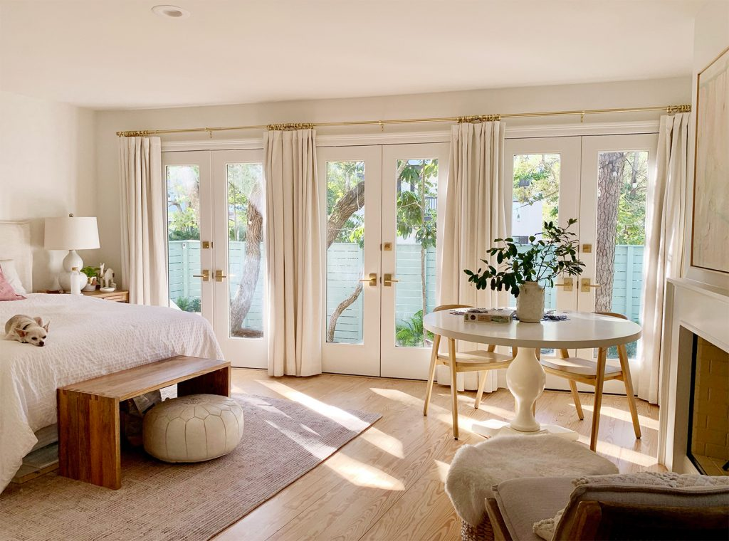 Bedroom with three french doors with with curtains and sunlight coming in