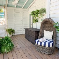 Full View Of Covered Porch With Plants Everywhere And Dog Sleeping In Egg Chair