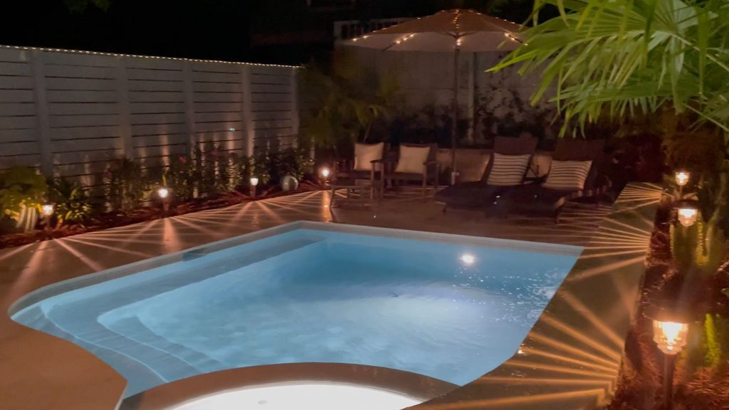 Small freeform pool at night with pool lights and solar lights on