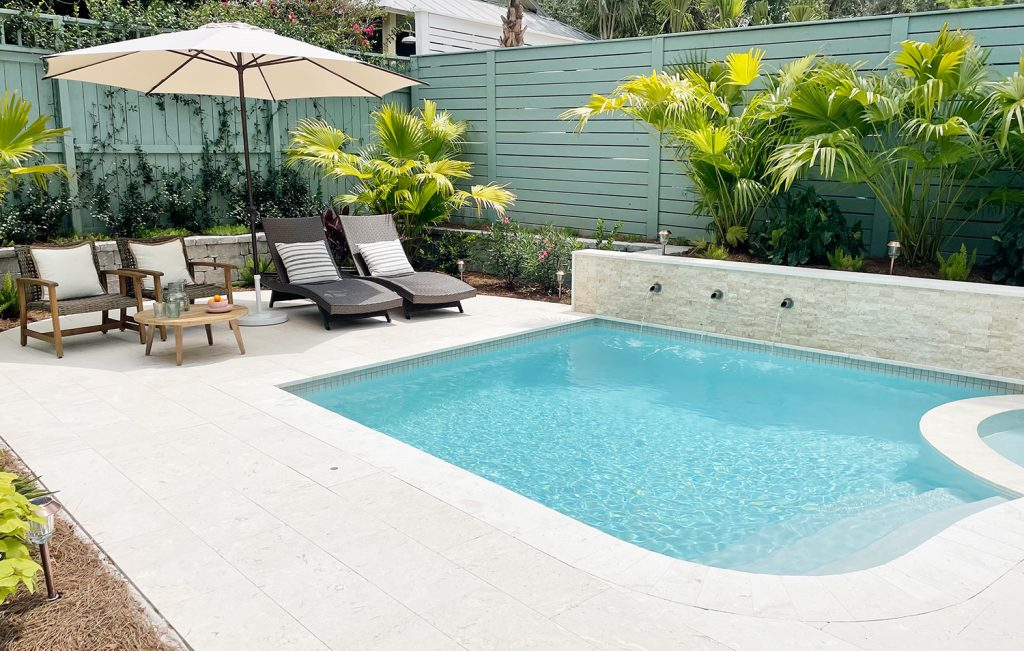 Small freeform pool enclosed by green fences with DiamondBrite Ivory plaster and shellstone travertine