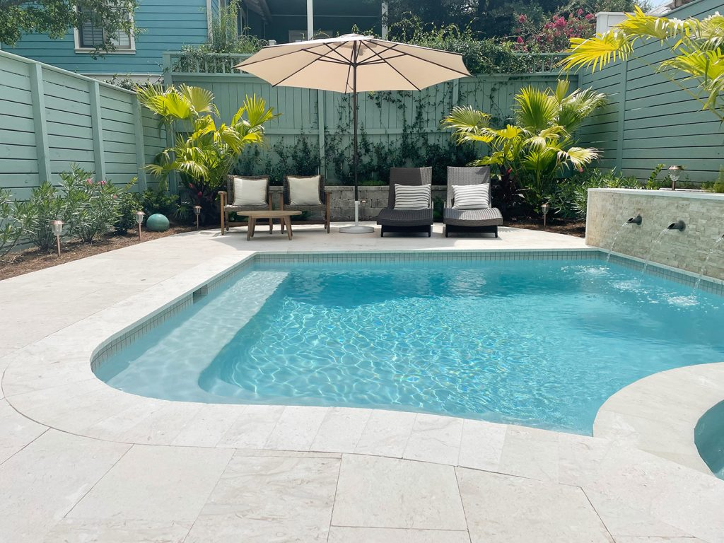 Curved edge pool with seating area in the background with green fences
