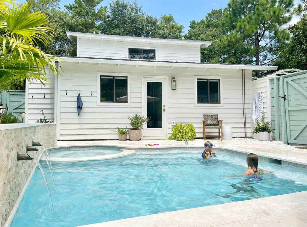 After photo of children playing in small freeform Florida pool with small white house in the background