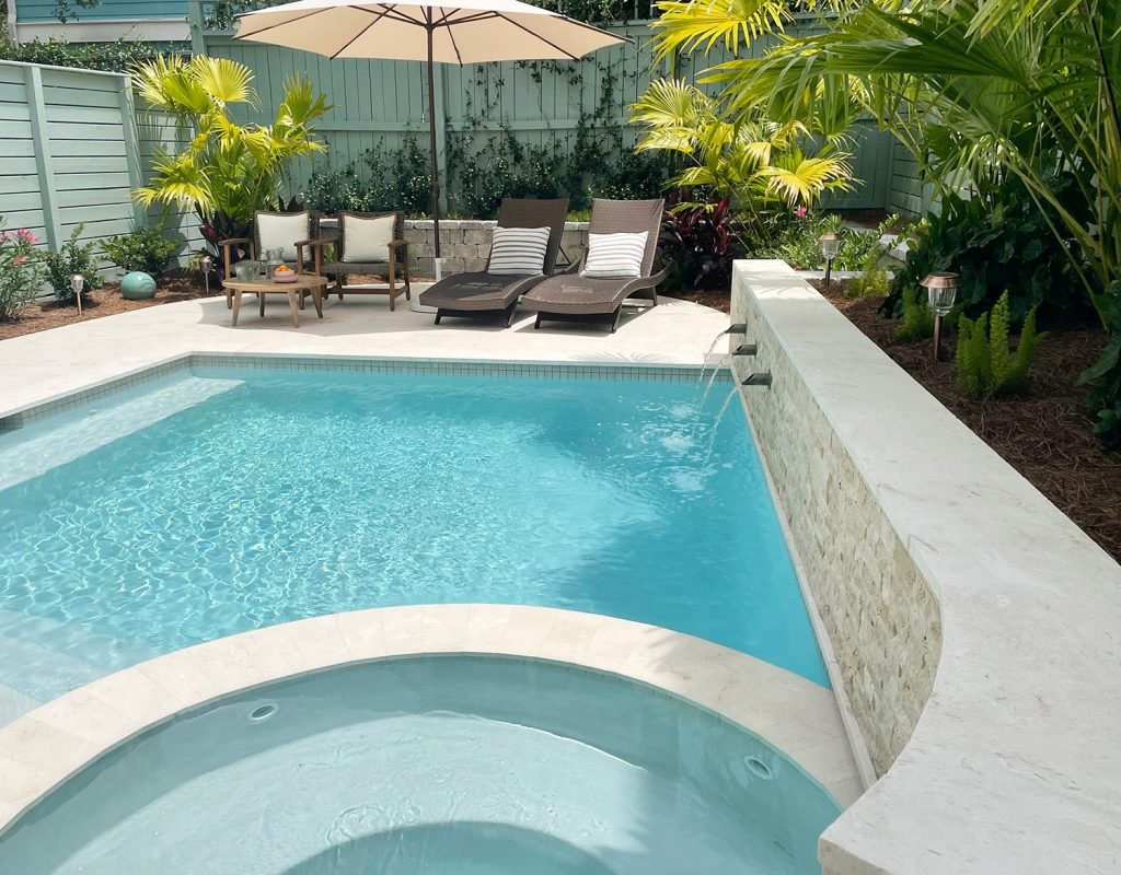 View of curved tile accent retaining wall covered in stone with fountains into pool