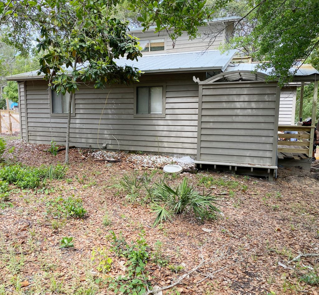 Before photo of house brown with same empty backyard