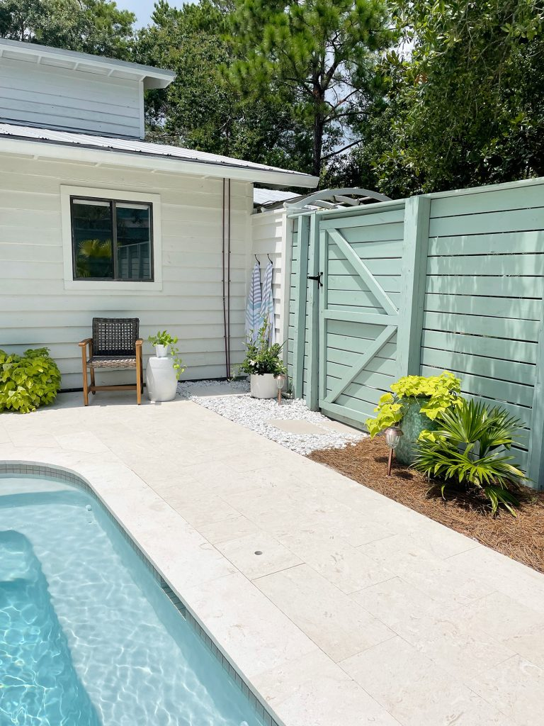 Horizontal slat gray green wood fence around pool area with gate near house
