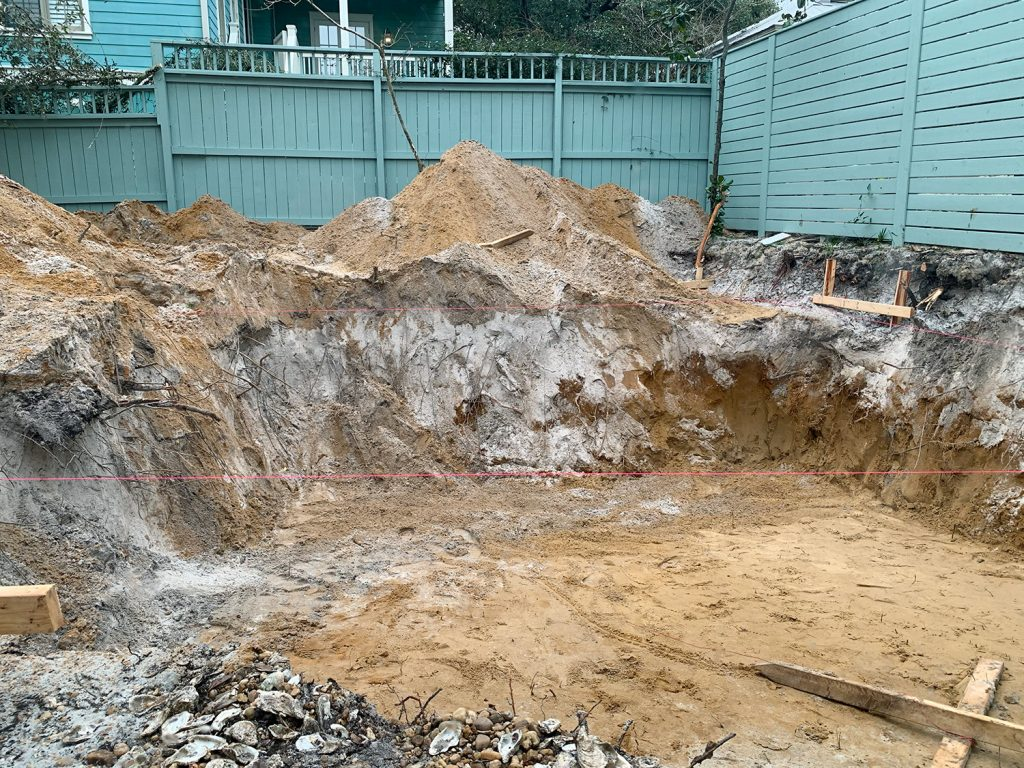 Large dirt hole dug in backyard where pool will be constructed
