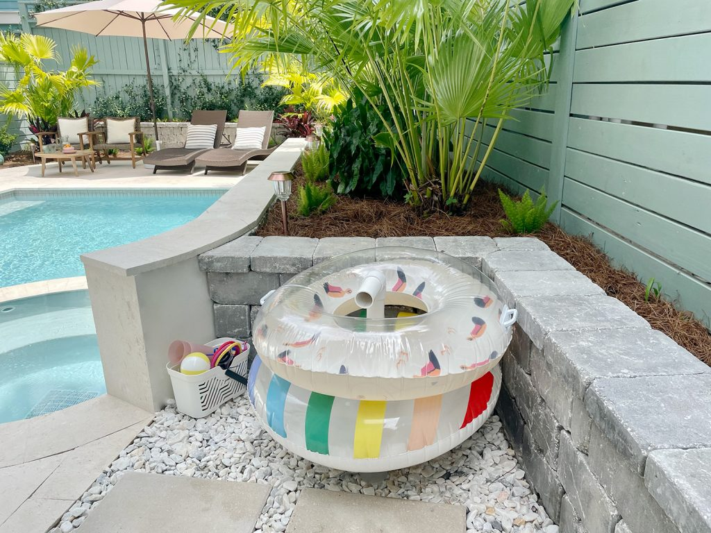 Pool floats organized on PVC pipe stand behind retaining wall