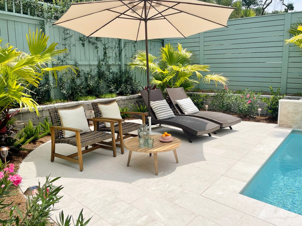 Round pool patio area surrounded by tropical plantings Chinese palms oleander jasmine stonecrop foxtail ferns