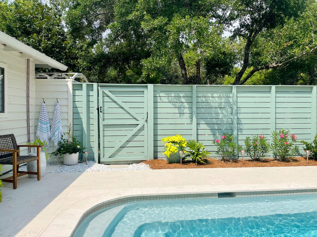 Pool fence with horizontal slats and gray green paint with planting bed in front