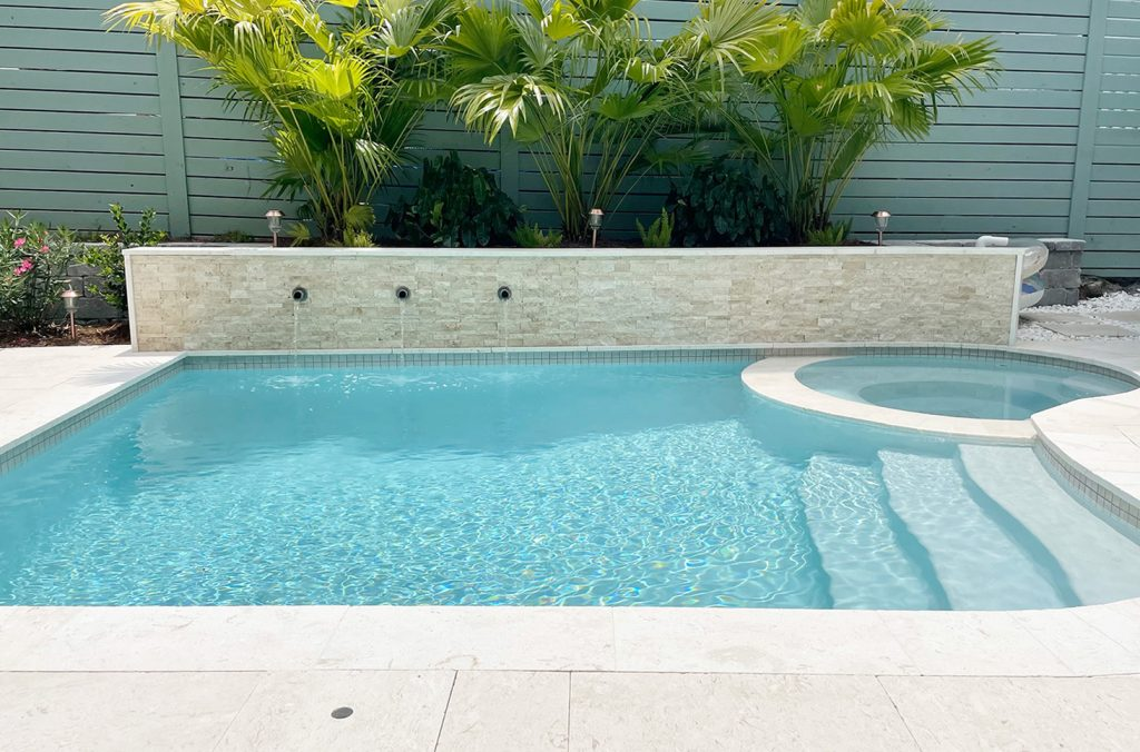 Small freeform pool with accent stone tile retaining wall flanked by gray block retaining wall