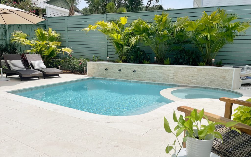 Widest view of full pool with round spa stone accent wall with fountains and tropical landscaping DiamondBrite Ivory plaster