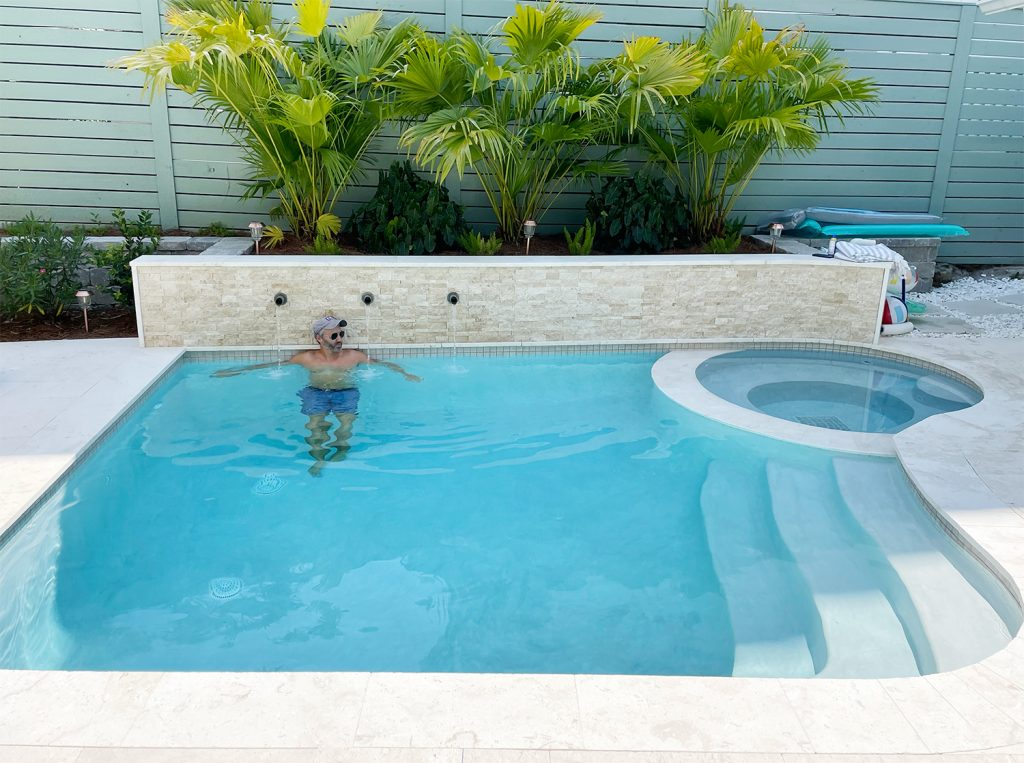 John in small freeform pool against stone accent retaining wall under palm plants