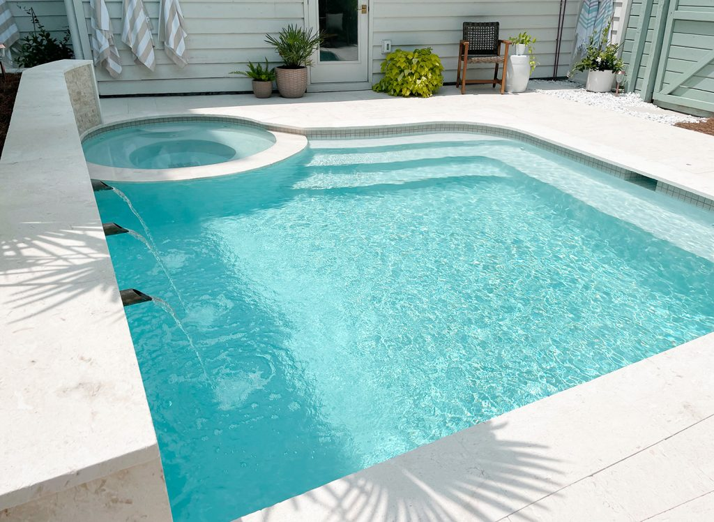 Angled view of small freeform pool with stairs at one end and bench across one end showing Ivory DiamondBrite plaster