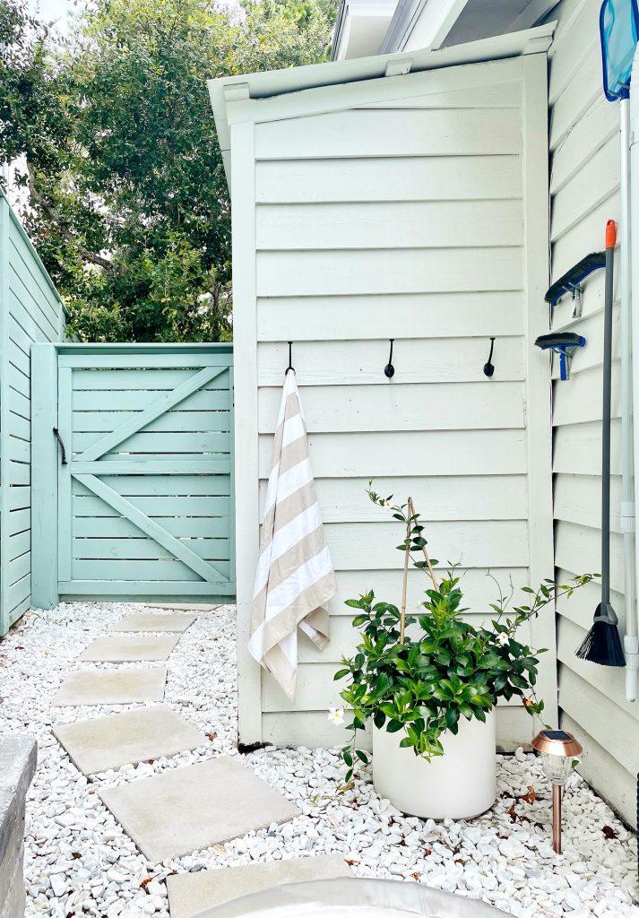 Hook towel storage along white shed and pool skimmer hanging on hooks on house siding