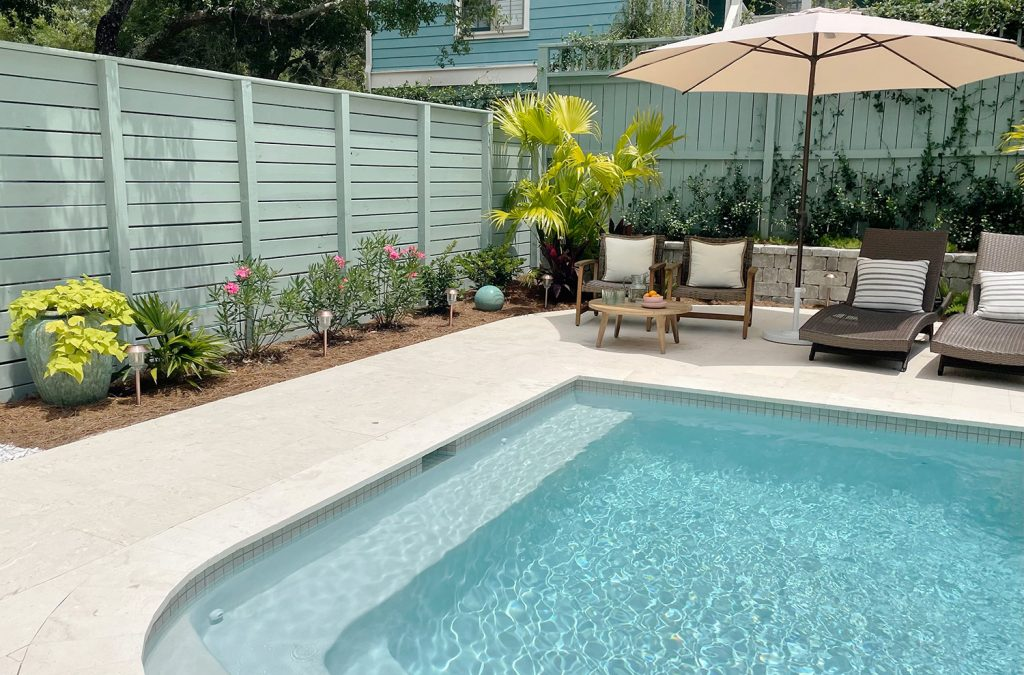 Two gray green painted wood fences surrounding pool at different heights