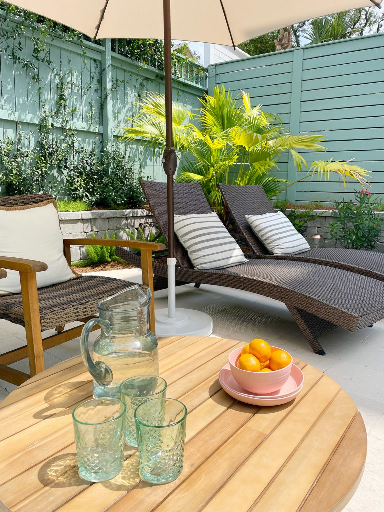 Pool patio area with brown chairs and wicker lounge chairs under umbrella