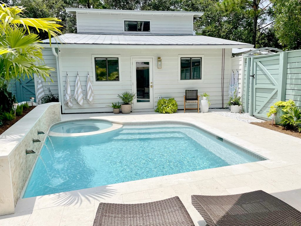 Small freeform pool with white house metal roof in background