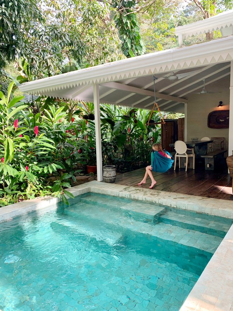Inspiration photo of small tropical pool next to white house and child in swing