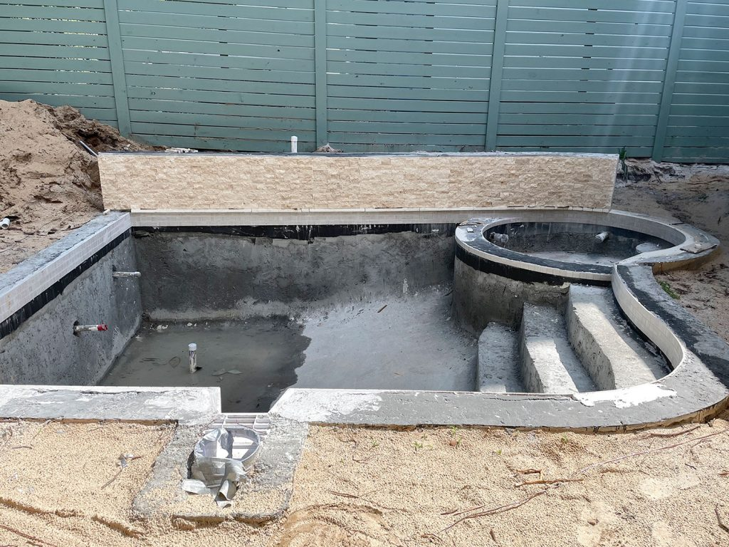Concrete pool with tile applied around waterline and across accent retaining wall