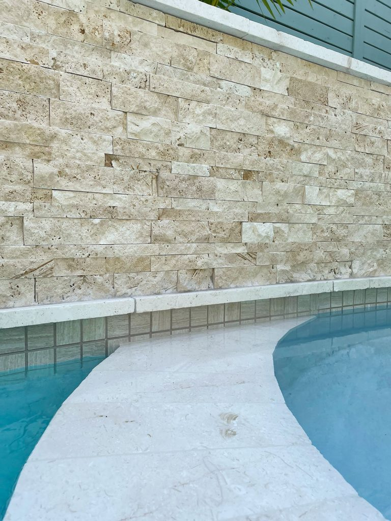 Detail photo of accent wall stacked natural stone tile and neutral waterline tile