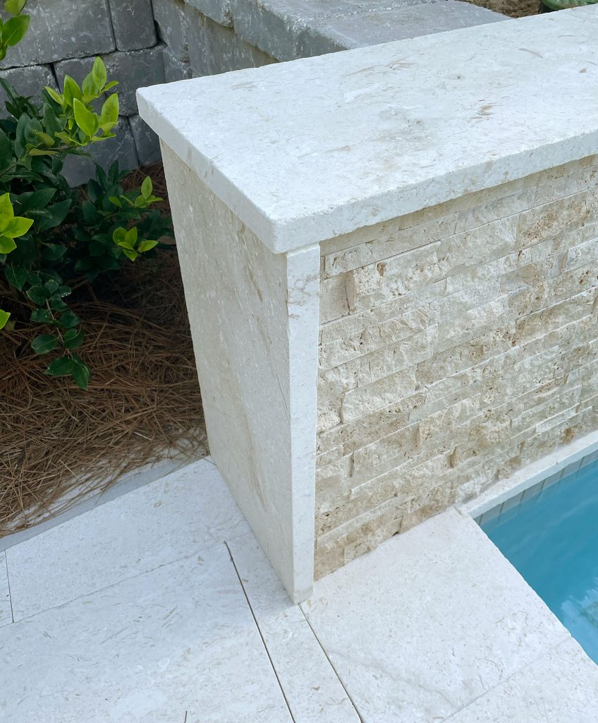 Detail photo of shellstone travertine patio tile used along the side and top of tile accent wall