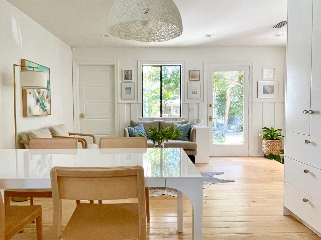 View Towards Sitting Area With White Modern Dining Table And Wood Chairs