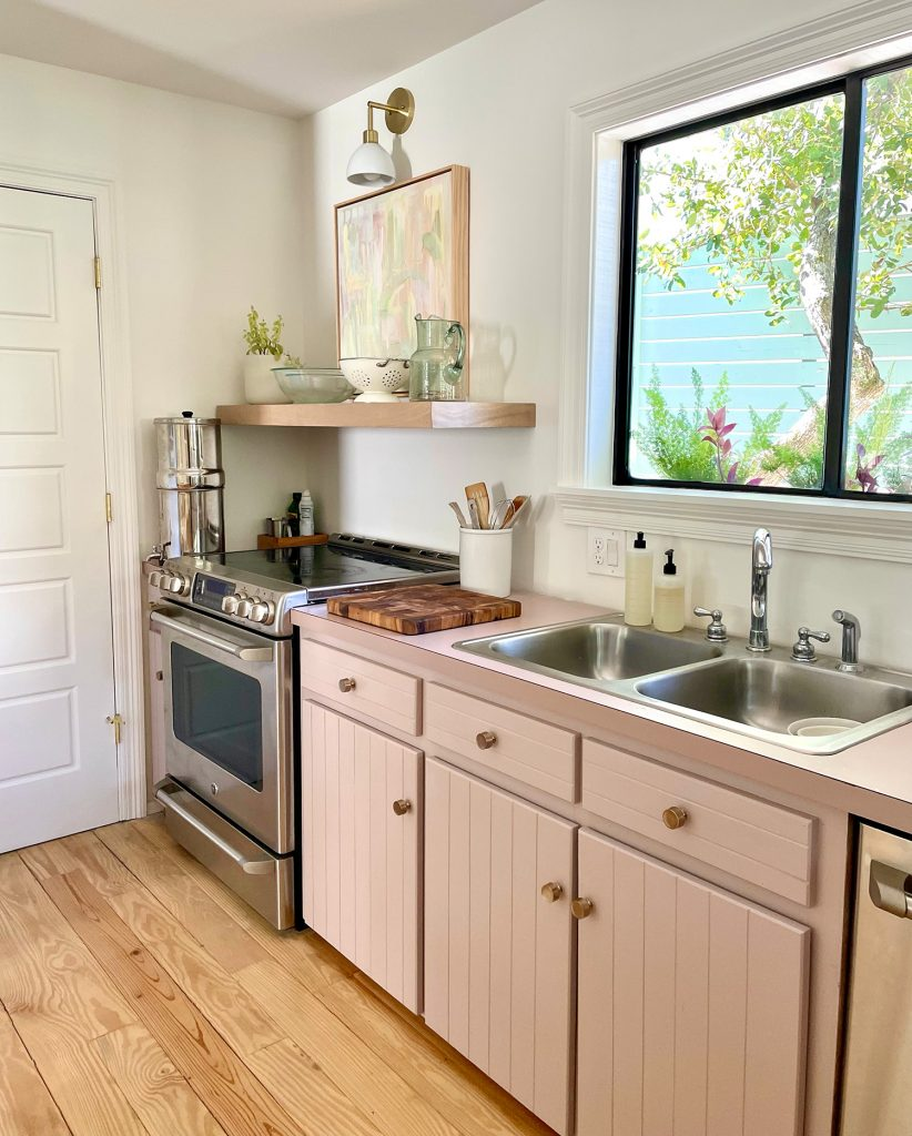 Beachy Kitchen With Mauve Pink Cabinets And Wood Floating Shelves With Mid Century Modern Lights