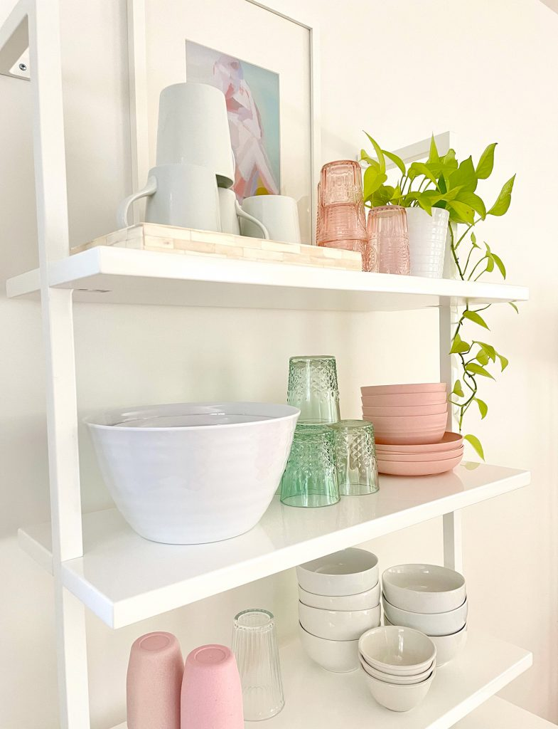 Detail View Of CB2 Floating Ladder Bookcase With Kitchenware On It