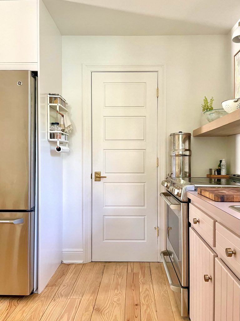 White Door To Kitchen Utility Closet With Spice Rack On Pantry Side