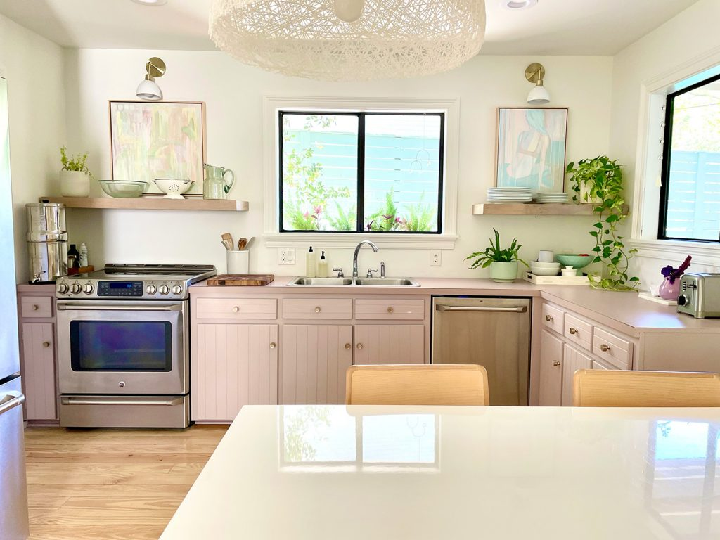 Straight View Of Beach Kitchen With Pink Mauve Cabinets And Floating Shelves